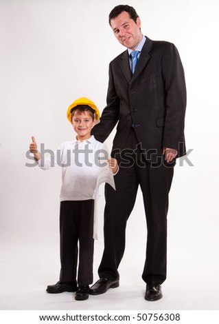 Cute cheerful boy with thumbs up wearing a safety helmet and holding a plan with his dad - stock photo