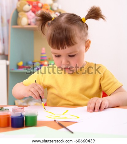 Cute cheerful child draws with paints in preschool - stock photo