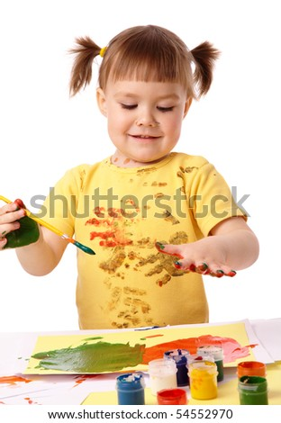 Cute cheerful child paint her fingers with colorful paints, isolated over white
