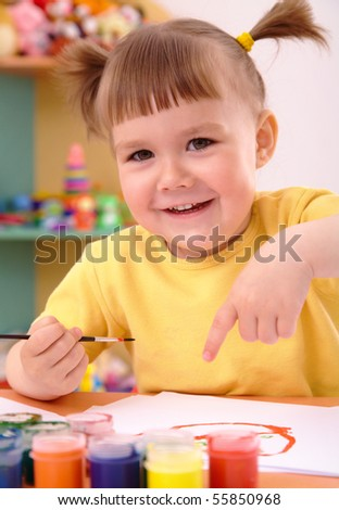 Cute cheerful child play with paints in preschool