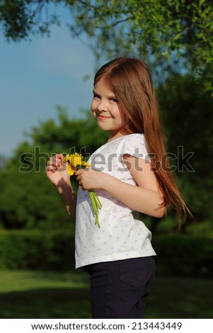 Cute cheerful child with a bouquet of daisies walks in the park on a background of beautiful green scenery