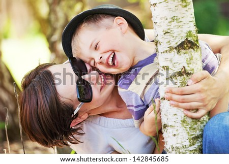 Cute cheerful child with mother play outdoor - stock photo