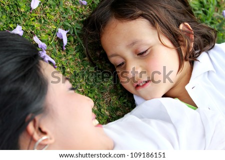 Cute cheerful child with mother play outdoors in the park - stock photo
