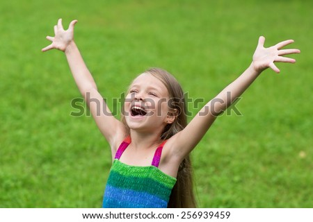 Cute cheerful girl seven years with open arms on the lawn. - stock photo