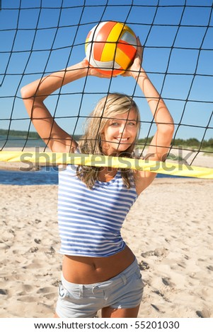 Cute cheerful girl with ball near volleyball net - stock photo