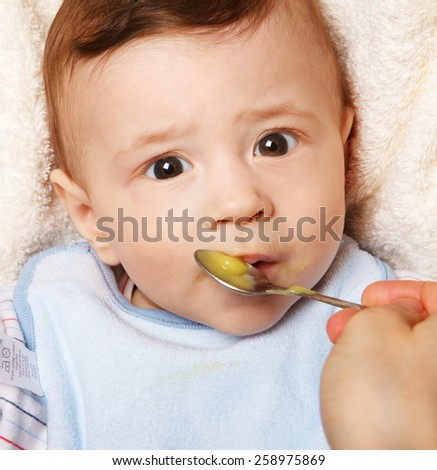 Cute cheerful  little baby boy eating.