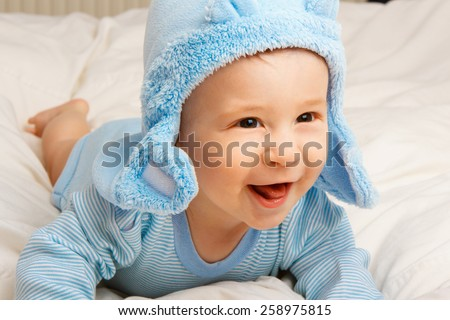 Cute cheerful  little baby boy in blue clothes. - stock photo