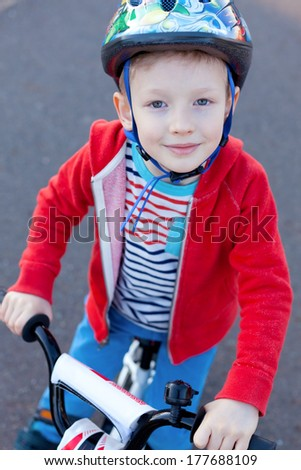 cute cheerful little boy in helmet riding bicycle - stock photo
