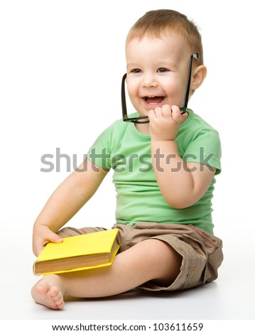 Cute cheerful little boy is playing with yellow book while wearing glasses, isolated over white - stock photo