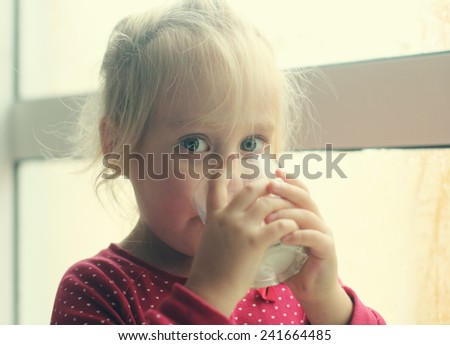 Cute cheerful little girl drinking milk - stock photo