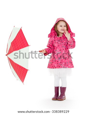 Cute cheerful little girl in raincoat and rubber boots with umbrella stands on a white background.  3 year old. - stock photo