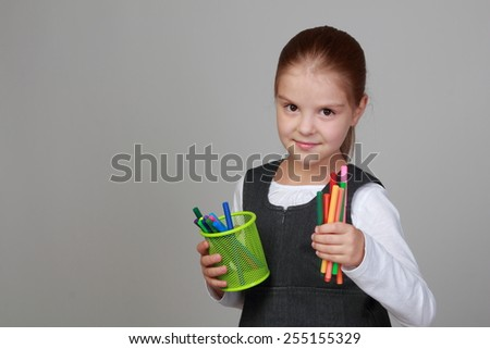 Cute cheerful little girl in school uniform holding a lot of of markers