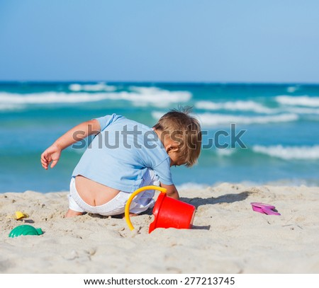 Cute child boy building sandcastle on the beach