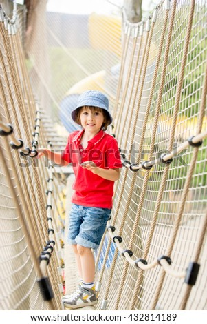 Cute child, boy, climbing in a rope playground structure, springtime - stock photo
