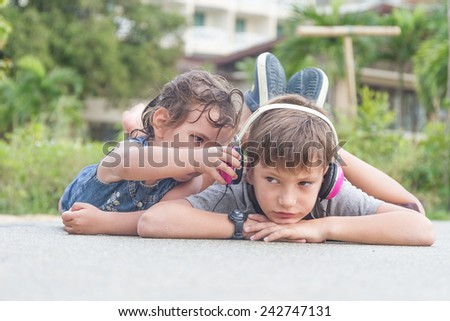 Cute child boy listening to music with headphones outside - stock photo
