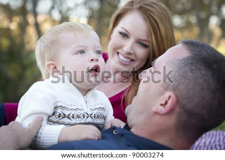 Cute Child Boy Looks Up to the Sky as Young Parents Smile. - stock photo