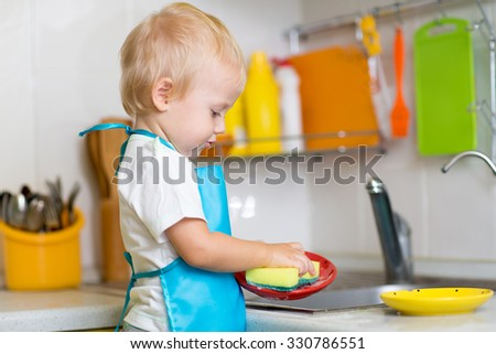 Cute child boy 2 years old washing dishes in kitchen - stock photo