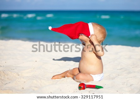 Cute child celebrating Christmas and New Year holidays in the Caribbean beach dressed as Santa. - stock photo