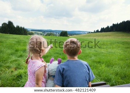 Cute child couple sitting on bench with view on mountains