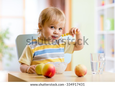 Cute child eating healthy food with with the left hand at home - stock photo