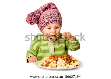 Cute child eating pasta; isolated over white - stock photo