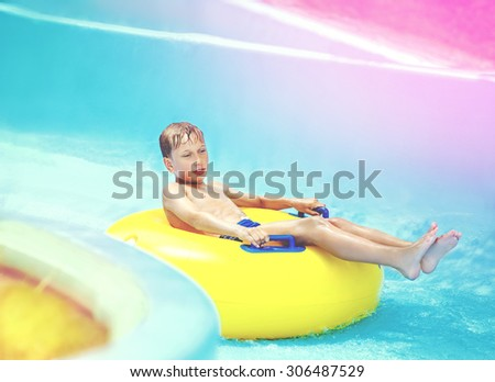 Cute child enjoying summer vacation in aqua park riding on yellow float - stock photo