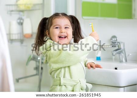 Cute child girl brushing teeth in bathroom - stock photo