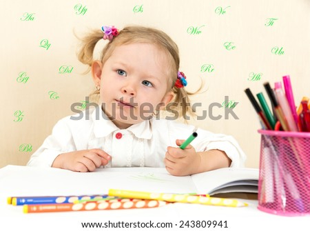 Cute child girl drawing with colorful pencils and felt-tip pen in preschool at table in kindergarten - stock photo