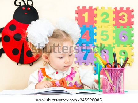 Cute child girl drawing with colorful pencils in preschool at table in kindergarten - stock photo