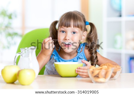cute child girl eating cereal with milk in nursery - stock photo