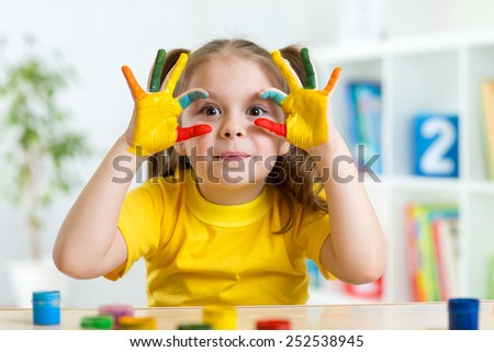 cute child girl have fun painting her hands