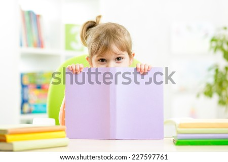 Cute child girl hiding behind book indoors - stock photo