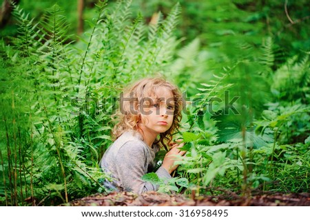 cute child girl hiding in ferns while playing in summer forest - stock photo