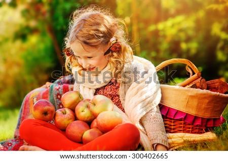 cute child girl holding apples in sunny autumn garden - stock photo