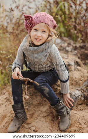 Cute child girl in knitted hat playing on the river side