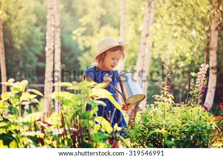 cute child girl in straw watering flowers in summer garden - stock photo