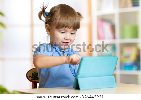 cute child girl playing with a digital tablet at home - stock photo