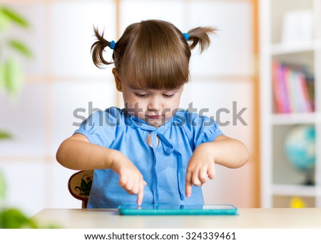 cute child girl playing with a digital tablet pc at nursery - stock photo
