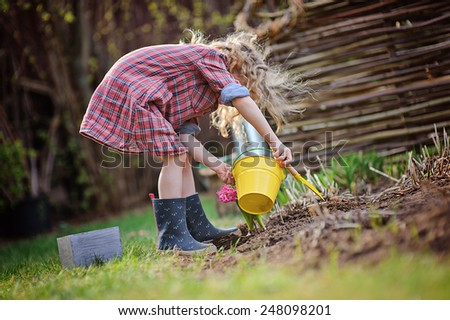 cute child girl plays little gardener and planting flowers in spring garden - stock photo