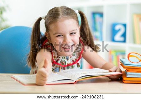 Cute child girl reading story from big book in nursery - stock photo