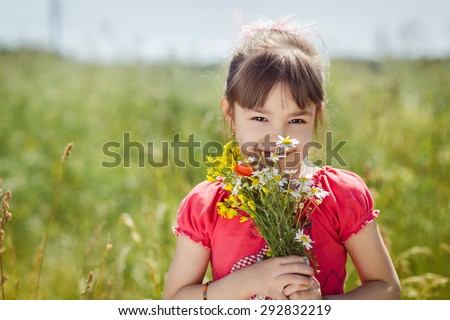 Cute child girl with bouquet of wildflowers - stock photo
