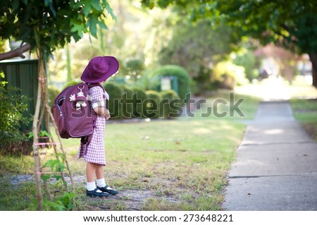 Cute child, happy little school girl, pupil of primary school in Australia, standing outdoors near pathway, ready to go to school for the first time - stock photo