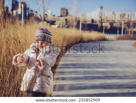 Cute child having fun in outdoors. New York city background - stock photo
