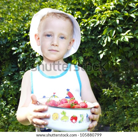 Cute child holding a bowl of strawberries - stock photo