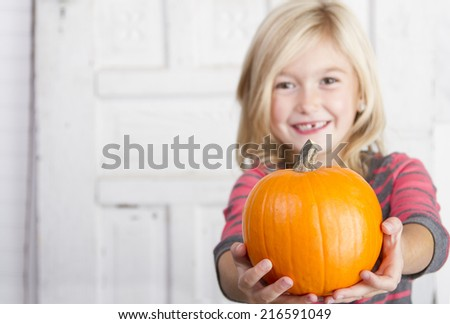 Cute child holding a small pumpkin - stock photo