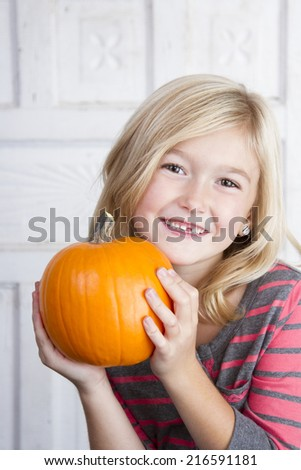 Cute child holding small pumpkin up by her face - stock photo