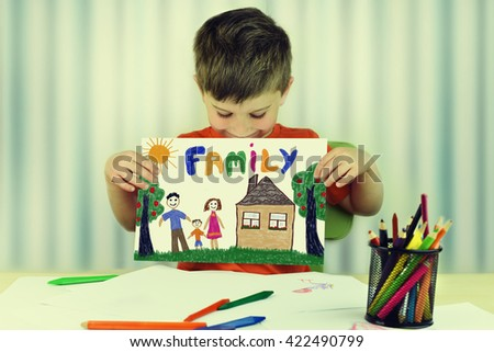 Cute child holds up drawing of a family