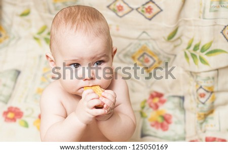 cute child learning to eat a biscuit - stock photo