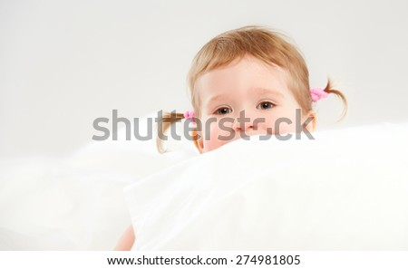 cute child little girl peeping from of pillows in bed - stock photo