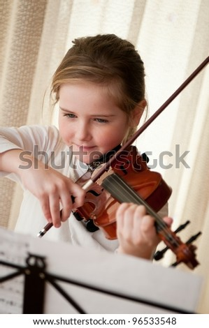 Cute child (little girl) playing violin and exercising at home - stock photo